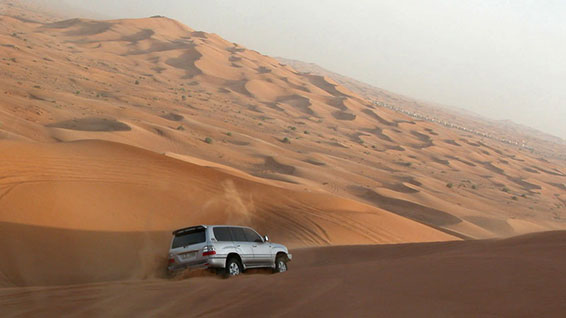 A car drives into a desert in Dubai.