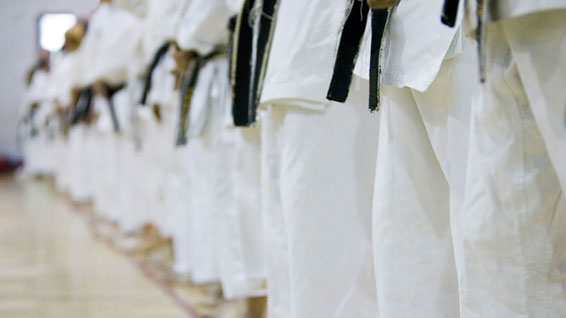 Legs and black belts of several karate practitioners.