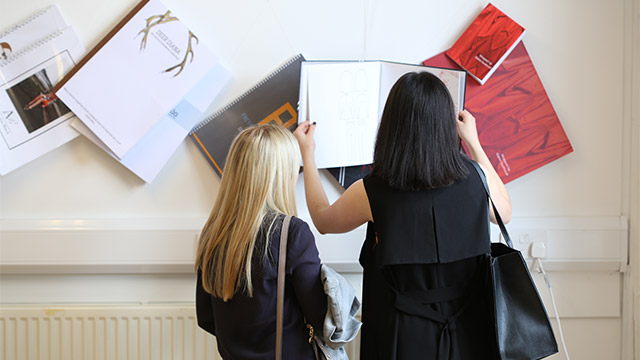 Visitors examining Textile and Design students' work