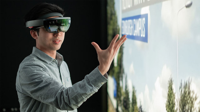 Male student wearing a virtual reality headset looking at his hand