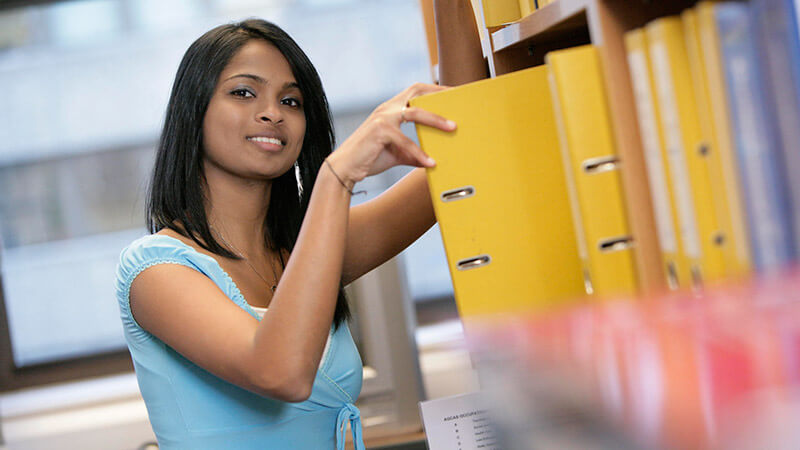 Female student looking through binders on shelves